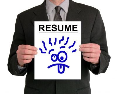 man holding resume with a funny face on it
